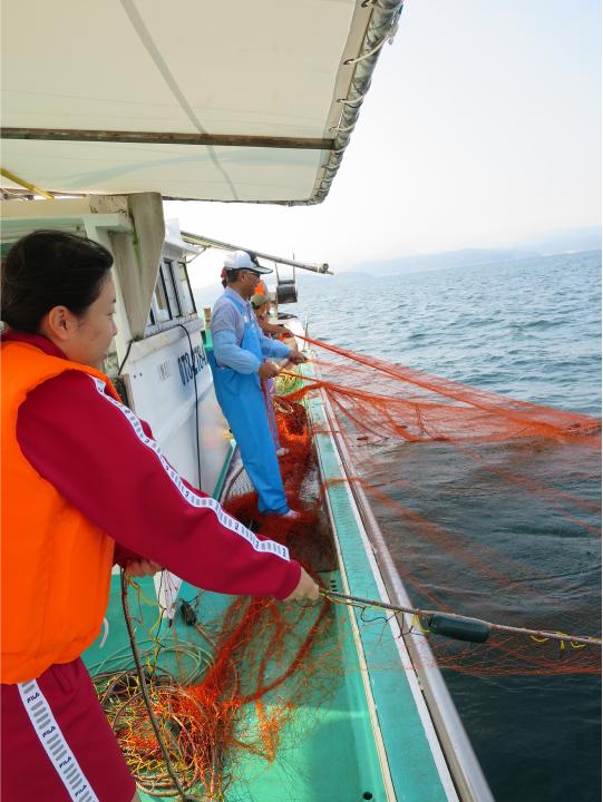 網を引き揚げる竹内さん